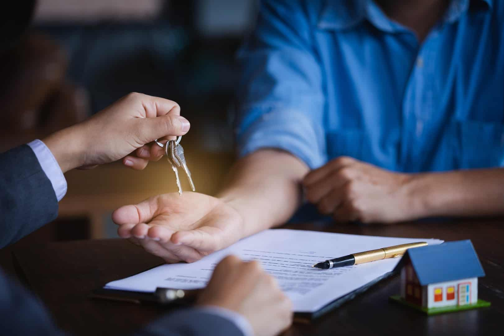 Real estate agent giving keys to new property owners after signing contract,concept agreement and Real estate concept.real estate, moving home or renting property.